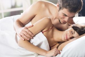 Young couple smiling and hugging at bedroom